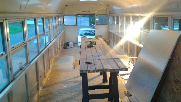 Installing wall insulation in school bus conversion